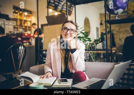 Tema profesión moderna para mujeres jóvenes. hermosa chica con gafas, sentado en la mesa de madera dentro de cafe. mano con pluma hace la entrada en el diario portátil