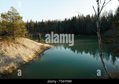 Joven toma fotos de viajes -hermoso lago Turquesa en Letonia - estilo Meditirenian colores en Estados bálticos - Lackroga ezers