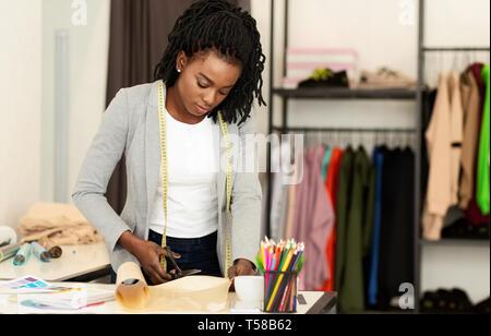 Diseñador de moda el trabajo en estudio, dibujo de corte