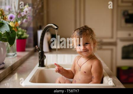 Bebé de tomar un baño en el lavabo de la cocina. Niño jugando con espuma y burbujas de jabón en el soleado baño con ventana. Chico del baño. Diversión en el agua para niños. Hygi