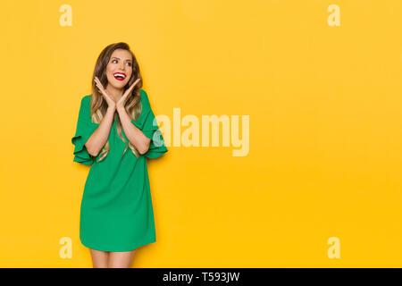 Hermosa joven en mini vestido verde está manteniendo la cabeza entre las manos, mirando a otro lado y riendo. Tres cuartos de longitud foto de estudio sobre fondo amarillo.