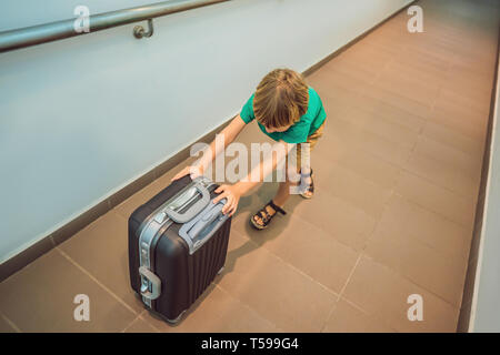 Chico divertido ir en viaje de vacaciones con la maleta en el aeropuerto, en interiores Foto de stock