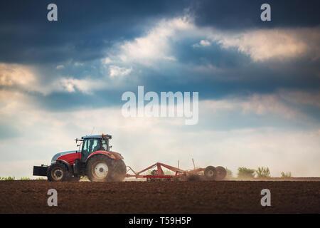 El agricultor prepara la tierra del tractor con el cultivador de semilleros