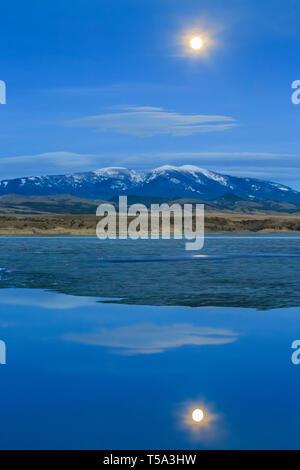 Luna llena ascendiendo detrás de monte Baldy sobre hielo ruptura en Canyon Lake ferry cerca de Townsend, Montana Foto de stock