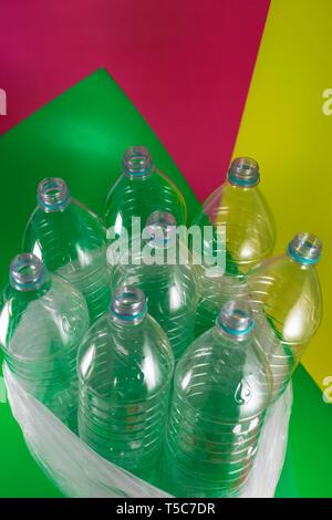 Un pack de 8 vacíos y botellas de agua de plástico reciclable, sin tapas, sello azul, en una bolsa de plástico, sobre un verde mar vibrantes colores geométricos, vino Foto de stock
