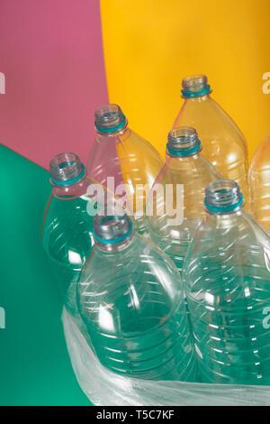 Un paquete de 7 vacíos y botellas de agua de plástico reciclable, sin tapas, sello azul, en una bolsa de plástico, en un mar de tonos color pastel verde, rosa suave Foto de stock
