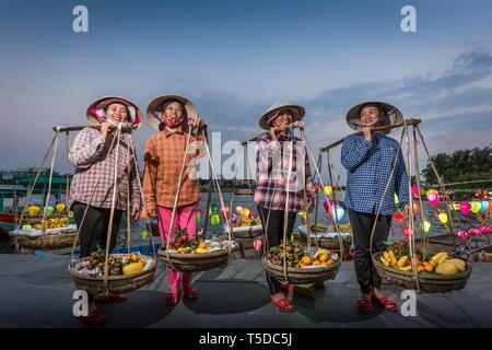 Hoi An, Vietnam - 21 de febrero de 2019: Las mujeres vietnamitas, frutas vistiendo sombreros cónicos de los proveedores tradicionales de transporte para el hombro y polo en Hoi An