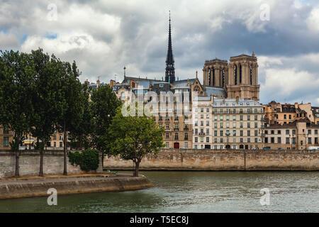 Vista del río Sena y la torre de la famosa catedral de Notre-Dame de París entre edificios típicos parisinos bajo el cielo nublado.