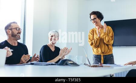 Los empresarios de las palmas después de la exitosa sesión de lluvia de ideas en la sala de juntas. Grupo de hombres y mujeres aplaudiendo tras la reunión productiva.