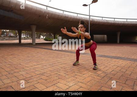 Mujer haciendo ejercicios en cuclillas en la ciudad 4k
