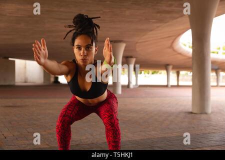 Mujer joven haciendo ejercicio sentadilla bajo un puente