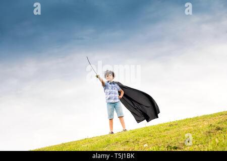 Orgulloso joven jugando el super héroe Vistiendo un manto caseras y blandiendo una espada de juguete en el horizonte contra un cielo azul