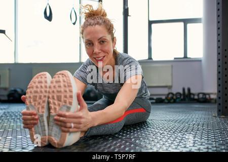 Un gran progreso. Joven bella mujer en ropa deportiva haciendo el estiramiento en la parte frontal de cristal en el gimnasio