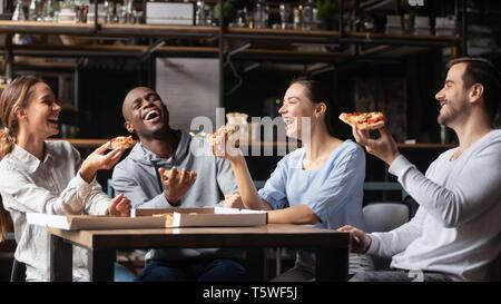 Amigos multirraciales riendo comer pizza reunidos en pizzería Foto de stock