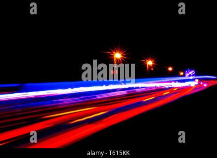 Coches estelas de luz sobre una carretera curvada en la noche. Tráfico nocturno senderos. Desenfoque de movimiento. Ciudad de noche carretera con tráfico de movimiento de faro. Paisaje urbano. Luz arriba