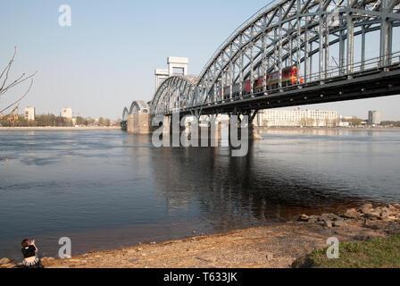 San Petersburgo, Rusia - Abril 26, 2019: La niña toma imágenes del tren sobre el puente de ferrocarril de Finlandia que cruzan el río Neva en San Petersburgo
