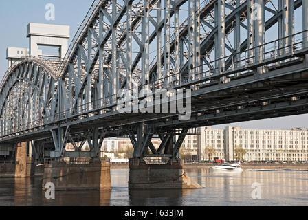 San Petersburgo, Rusia - Abril 26, 2019: un pequeño barco blanco sobre el río Neva, cerca de la Finlandia de un puente de ferrocarril en San Petersburgo