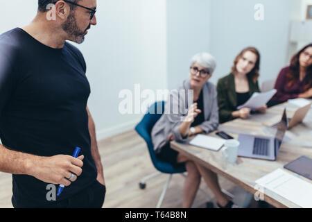 Empresario hablando con colegas durante una reunión en la oficina. Ejecutiva madura escuchar las sugerencias de su equipo durante una presentación.