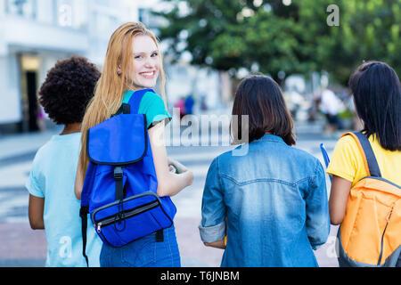Joven estudiante femenina en inglés con un grupo de amigos, la piscina en el verano en la ciudad