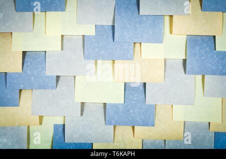 Pared cubierta con notas de papel colorido. Textura de papel en blanco.