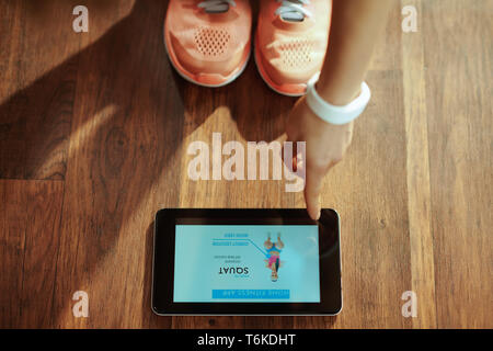 Closeup en saludable Deportes mujer en ropa de gimnasia en la moderna sala de estar con hogar workout trainer app en Tablet PC. Foto de stock