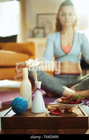 Primer plano sobre la bandeja con cosas para la fragante aroma yoga y colocar mujer meditando en el fondo de la casa moderna.
