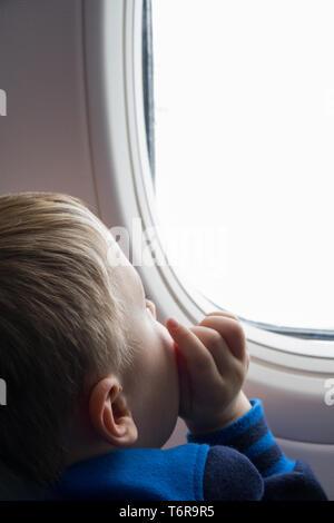 Chico mirando a través de la ventana de avión Foto de stock