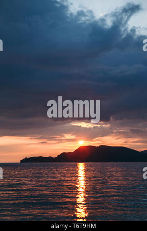 Hermosa vista de la puesta de sol o amanecer y el paisaje natural con el mar y las colinas o montañas de Montenegro en el verano.