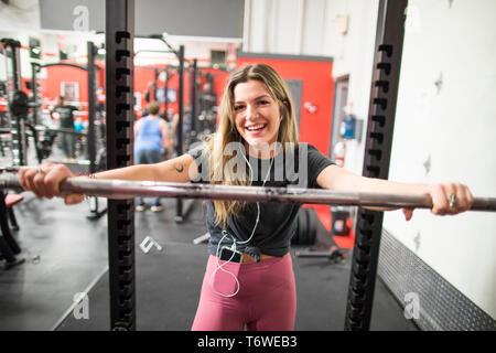Mujer sonriente apoyado en barbell en el gimnasio