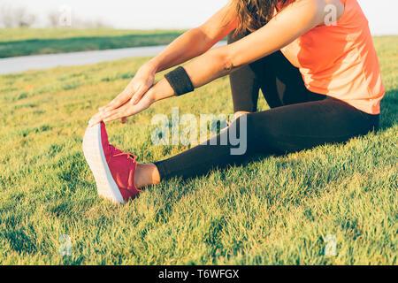 Mujer joven corredora estirar las piernas antes de ejecutar en un parque. Cerrar el Athletic y saludable niña vestidos de blanco y rosa sneakers.