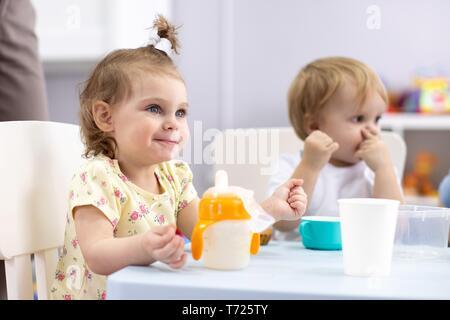 Adorable niña niño beber leche de vaca para desayunar. Niño sano consumir leche como fuente de calcio en la salud. Los niños comen en vivero o guardería en la mañana.