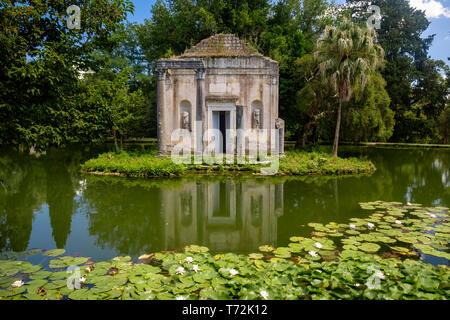 """El jardín inglés del """"Reggia di Caserta' tiene unas cuantas falsas ruinas, como este templo ruina en una pequeña isla en medio de un estanque con nenúfares."""