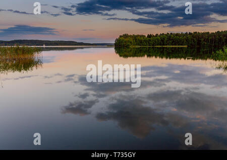 Puesta de sol sobre el lago masuria Pluszne cerca del pueblo de Olsztynek.: Hohenstein (GER). Provincia Warmian-Masurian, Polonia.