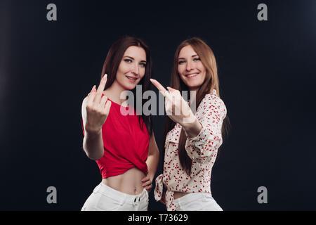 Dos niñas en ropa casual gesticulando con los dedos.