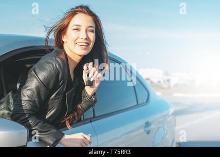 Happpy hermoso cabello largo morena encantadora joven mujer asiática en la chaqueta de cuero negro con la llave en la ventana de coche