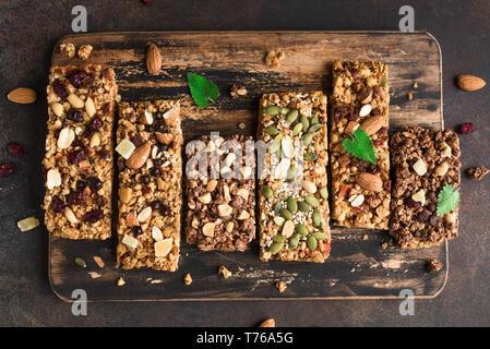 Varias barras de granola en oscuro fondo rústico, vista superior. Refrigerio saludable - granola casera súper alimento bares.