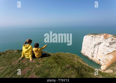 Francia, Normandía: Madre e hijo sentado sobre el césped cubierto de roca acantilados por encima del arco de Playa Etretat