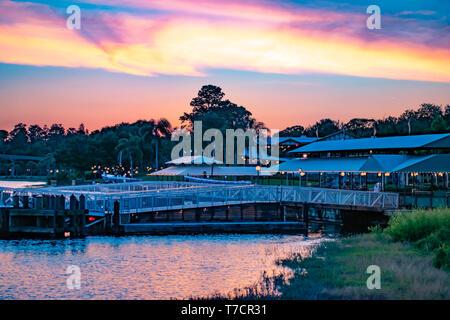 Orlando, Florida. El 23 de abril de 2019. Magic Kingdom wharf y bosque verde sobre fondo colorido atardecer en Walt Disney World area .