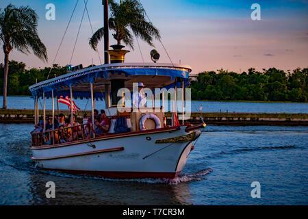 Orlando, Florida. El 23 de abril de 2019. Taxi acuático que llegan a la costa y palmeras en colorido atardecer antecedentes en el área de Walt Disney World.