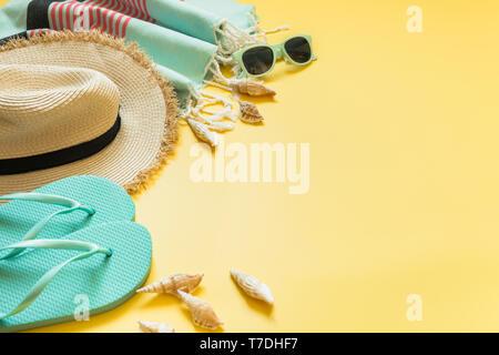Ropa de playa y vacaciones tropicales, sombrero de paja, toalla, gafas de sol en amarillo con espacio para el texto. Concepto de verano.