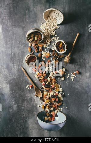 Variedad de frutos secos, miel y copos de avena, vierte en el cuenco de cerámica para cocinar saludable desayuno casero muesli o granola y barritas energéticas a través de bl.