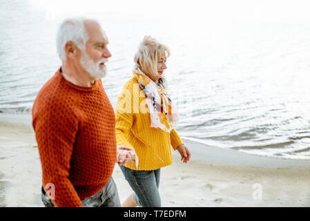 Encantadora pareja senior vestidas con coloridos suéteres caminando por la playa, disfrutar de tiempo libre durante la jubilación cerca del mar