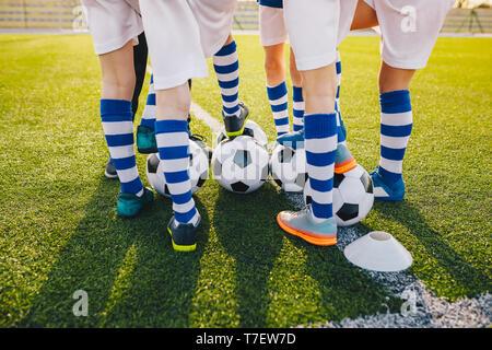 Grupo de jóvenes jugadores de fútbol en entrenamiento de fútbol. Las piernas de niños pateando balones de fútbol en el campo. Atardecer de verano en el fondo. Entrenamiento de fútbol bac