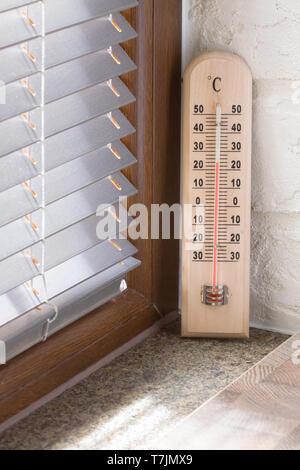 Un termómetro de madera con escala analógica midiendo la temperatura colocado cerca de la ventana
