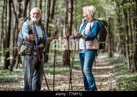 Hermosa pareja senior caminatas con mochilas y bastones de trekking en la selva. Concepto de la vida activa a la jubilación