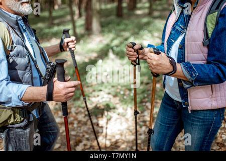 Hombre y mujer senior de senderismo con bastones de trekking en la selva, vista cercana con Cara recortada