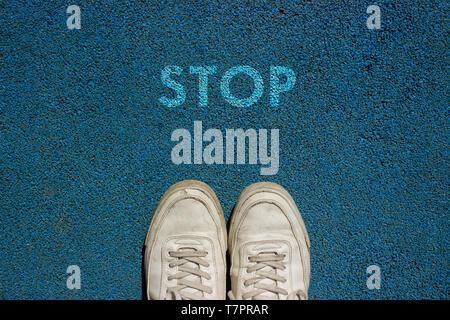 Nuevo concepto de vida, calzado deportivo y la palabra STOP escrita en azul a Pie TIERRA, slogan de motivación.