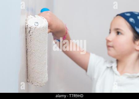Niña con rodillo de pintura en la mano. Los niños ayudando a los quehaceres de la casa concepto