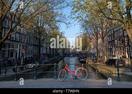 Parking de bicicletas rojo sobre el puente sobre las tranquilas aguas de un canal con un barco dando un viaje de ida y vuelta a los turistas, Ámsterdam, Países Bajos