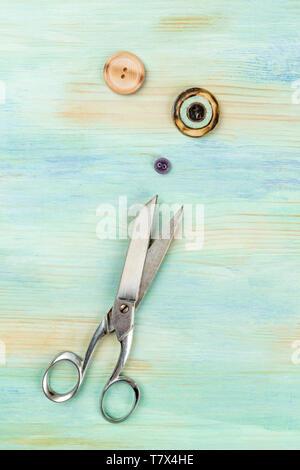 Vintage tijeras y botones, disparó desde arriba sobre un fondo de color verde azulado con espacio de copia